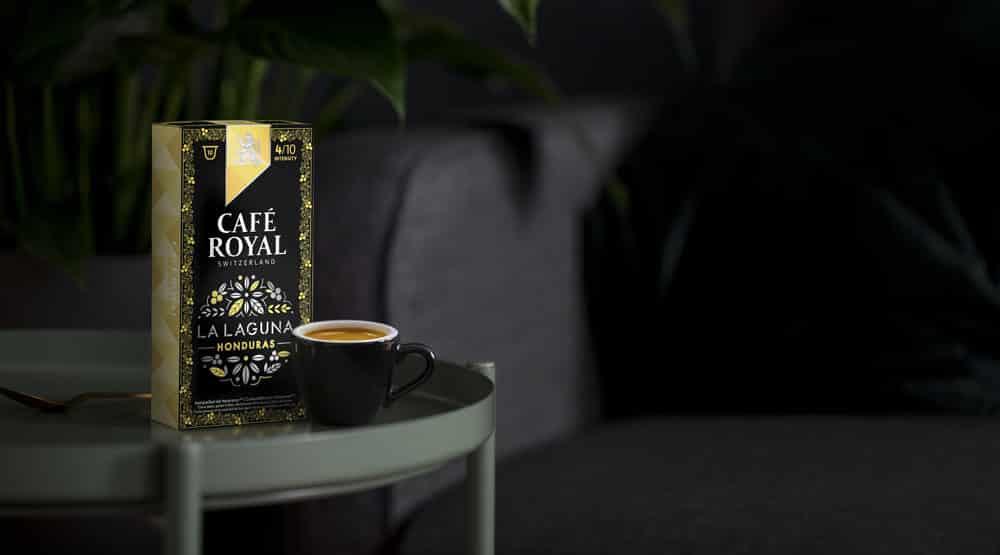 un paquet de Café Royal est posé sur une table à côté d'une tasse de café