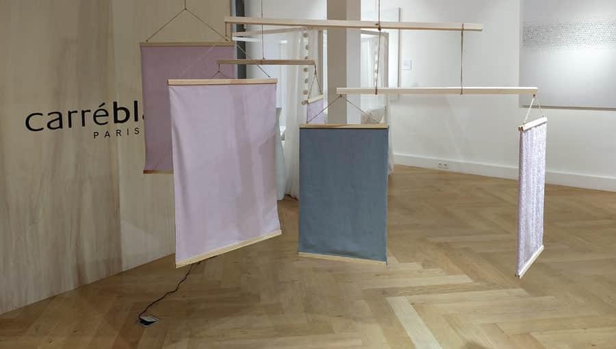 Des pans de tissus Carré Blanc sont exposés dans une salle