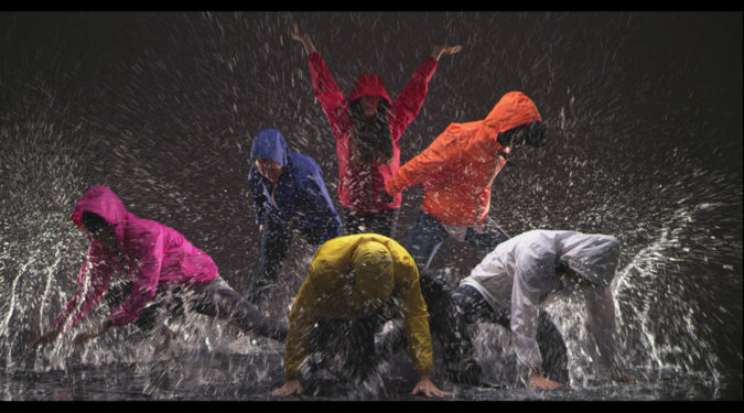 Artistes dansent en kway sur une scène détrempée
