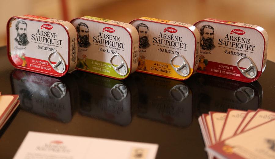Quatre boites de sardines Saupiquet alignées sur une table